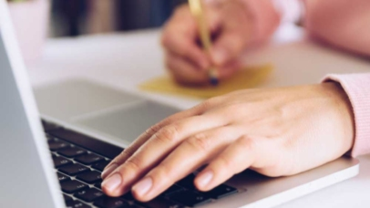 Laptop and Woman hands writing a note on a white marble desk